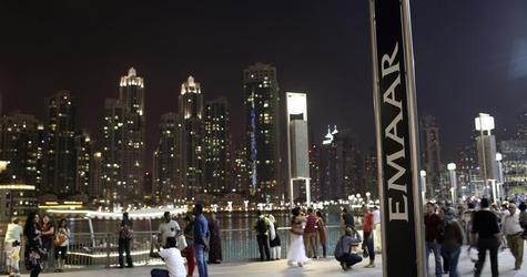 People have their pictures taken near an Emaar sign outside the Dubai Mall