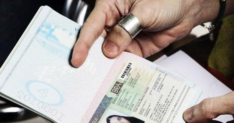 Cuba's best-known dissident, blogger Yoani Sanchez, displays her visa for Brazil at Havana's Jose Marti International Airport