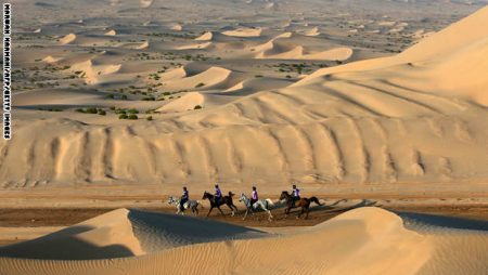 Participants ride horses across sand dunes during the Sheikh Sultan Bin Zayed al-Nahyan International Equestrian festival in the Boudthib Endurance Village near the Emirati capital Abu Dhabi on March 16, 2013. AFP PHOTO/MARWAN NAAMANI (Photo credit should read MARWAN NAAMANI/AFP/Getty Images)