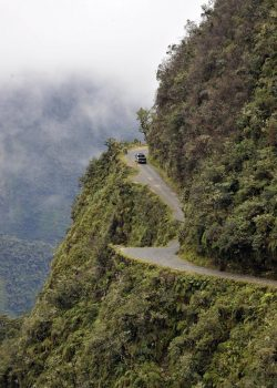 "A car drives on the ""death road"" --one of the world most dangerous-- along a steep ravine near Challa, Los Yungas region, 110 km north of La Paz, on February 9, 2012. The 400km-long road linking La Paz with Los Yungas, with stretches as high as 4,000 metre (13,100 feet) of altitude,  is so dangerous that is popularly known as ""death road"".   AFP PHOTO/Aizar Raldes (Photo credit should read AIZAR RALDES/AFP/Getty Images)"
