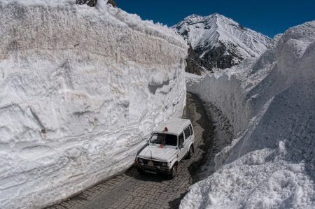 ZOJILA, KASHMIR, INDIA - APRIL 30: An vehicle  passes through the snow-cleared Srinagar-Leh highway on April 30, 2016 in Zojila, 108 km (67 miles) east of Srinagar, the summer capital of Indian administered Kashmir, India. The 443 km (275 miles) long Srinagar-Leh highway was opened for vehicles by Indian Border Roads Organisation after remaining snowbound at Zojila Pass for the past five months. The pass connects Kashmir with Ladakh region a famous tourist destination among foreign tourists for its monasteries, landscapes and mountains. The average snow buildup on the rocky territory of Zojila pass normally stays in the level of 15 to 25 meters and is closed for a half of each year. It opens up in late spring and travelers on the pass have to withstand snowstorms, fierce air currents, cold and highly dangerous circumstances. (Photo by Yawar Nazir/Getty Images)