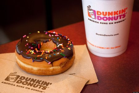 A chocolate glazed donut and a cup of coffee are arranged for a photograph at a Dunkin' Donuts Inc. store in West Orange, New Jersey, U.S., on Thursday, July 7, 2011. Sales at U.S. retailers surpassed analysts' estimates last month as discounts and lower gas prices in the U.S. enticed consumers to spend. Photographer: Emile Wamsteker/Bloomberg via Getty Images
