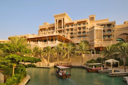 Dubai.  Al Qasr Hotel, built in the style of a Moroccan palace, seen over one of the Madinat Jumeirah's canals with an abra, a water taxi.