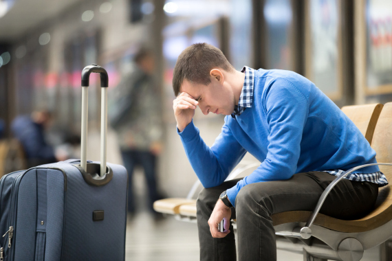 Portrait of young handsome guy wearing casual style clothes waiting for transport. Tired traveler man travelling with suitcase sitting with frustrated facial expression on a chair in modern station