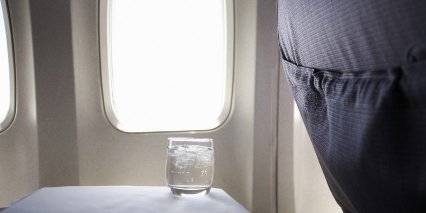 Glass of water on airplane tray table by window
