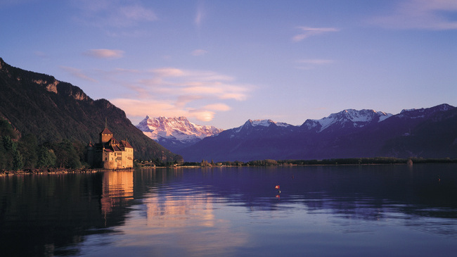 Switzerland is yours. Montreux. Dusk embraces Lake Geneva, Canton Vaud. In the background one can see Chillon Castle with Dents du Midi (3757 m). Ihre Schweiz. Montreux. Abendstimmung am Genfersee, Kanton Waadt. Das Schloss Chillon mit Dents du Midi (3257 m) im Hintergrund. A vous la Suisse. Montreux. Ambiance crepusculaire sur le lac Leman, canton de Vaud. Le chateau de Chillon avec les Dents-du-Midi (3257 m) au fond. Copyright by Switzerland Tourism                  By-line: ST/swiss-image.ch